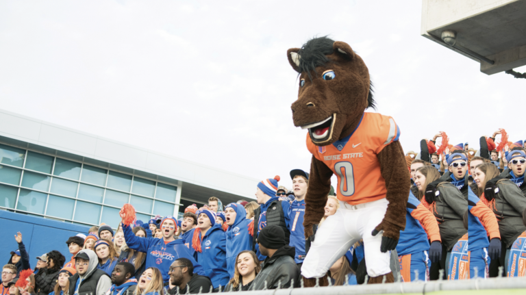 Buster Bronco at Football Game with students