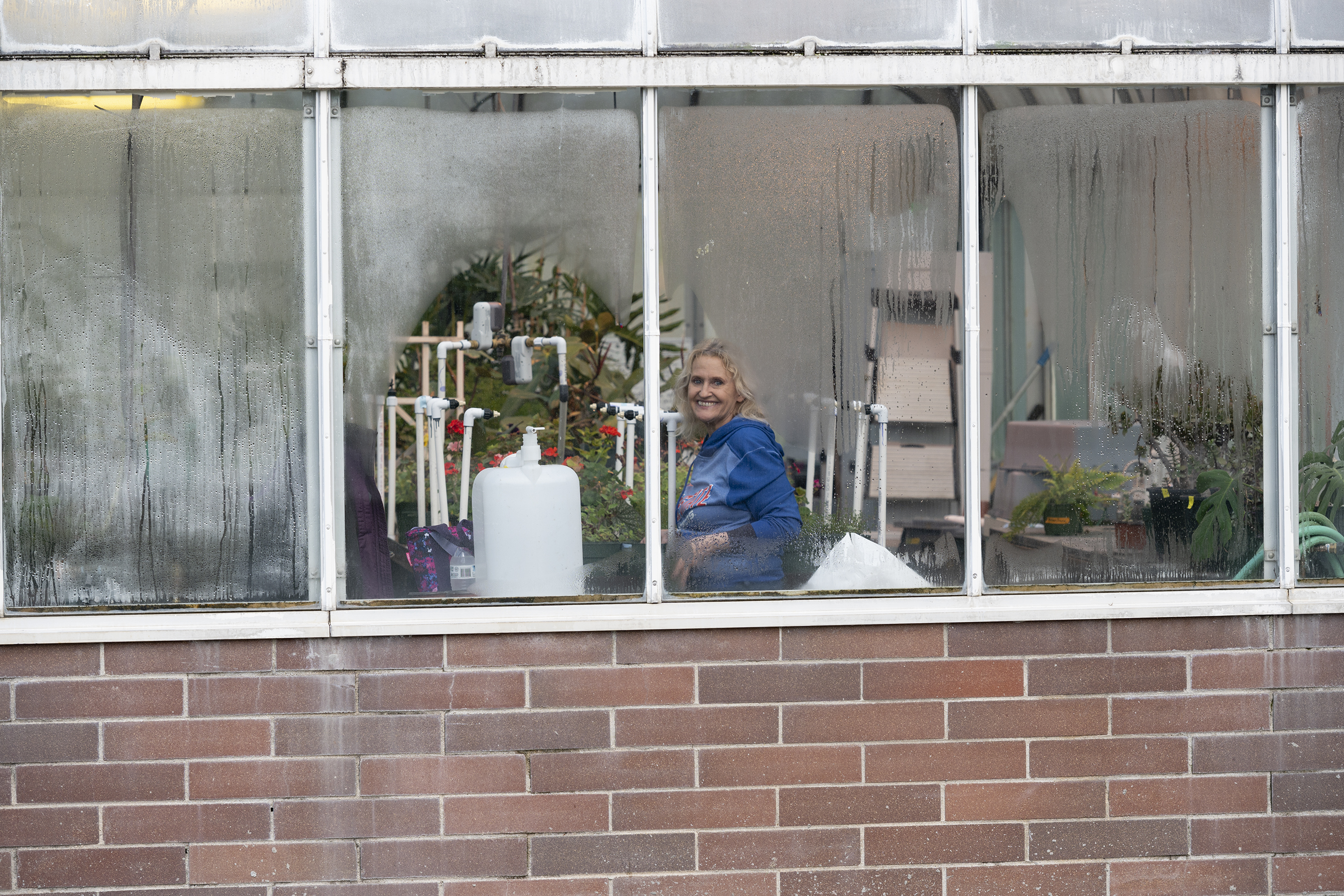 Tami Cox of the biology department tends to the plants in the teaching greenhouse. Photo, John Kelly
