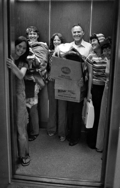 Family using elevator to transport things to a residence hall in the 1970s