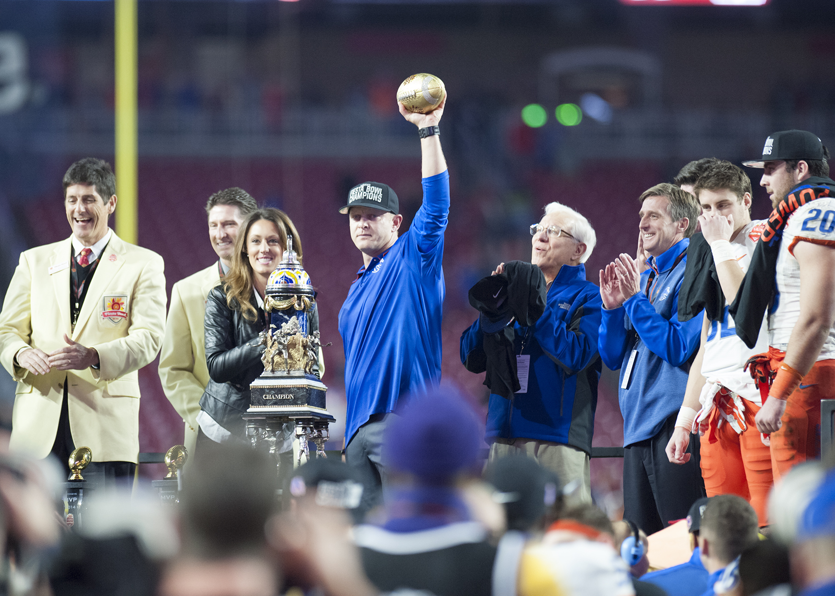 Coach Harsin holds football in the air at Fiesta Bowl