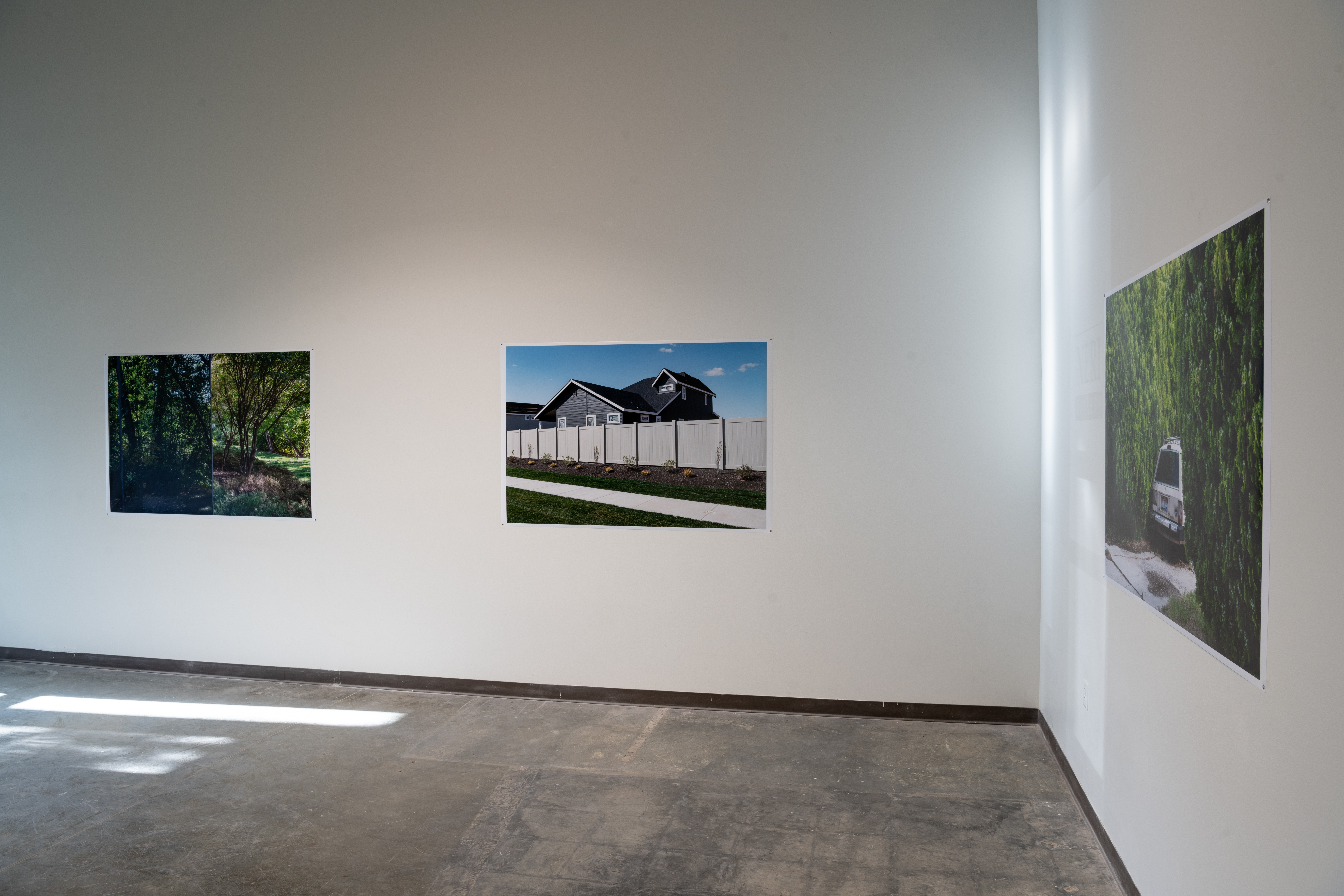 View of first 3 Zhang photos: left - diptych of trees, middle photo - blue sky over gray house behind a white fence, left - angled view of shrubs surrounding a the backyard of a car in a driveway.