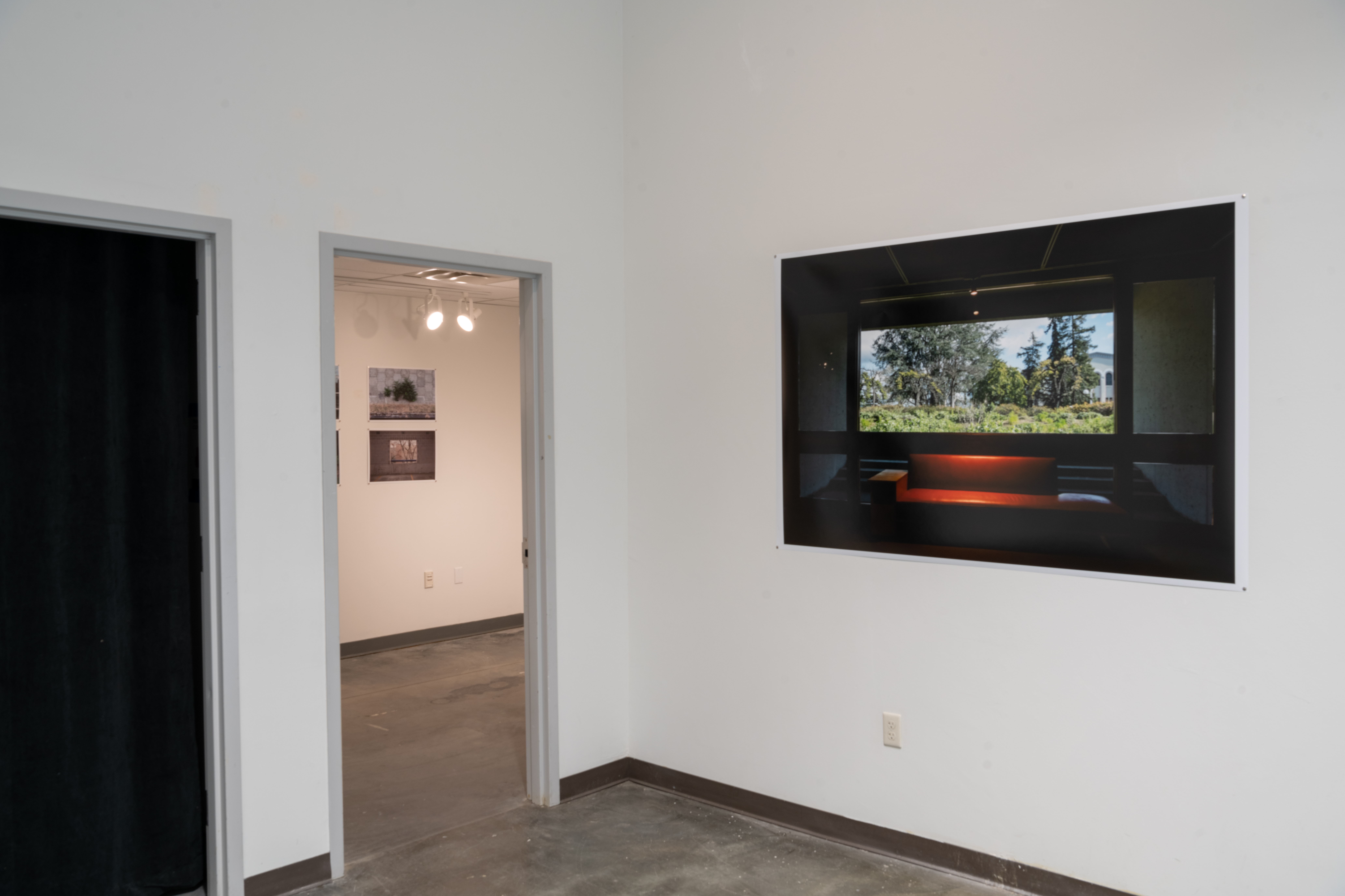 View of Zhang photo installation, right - photo of red leather sofa in front of projection of trees, and left - a doorway with multiple photos installed on the gallery wall.