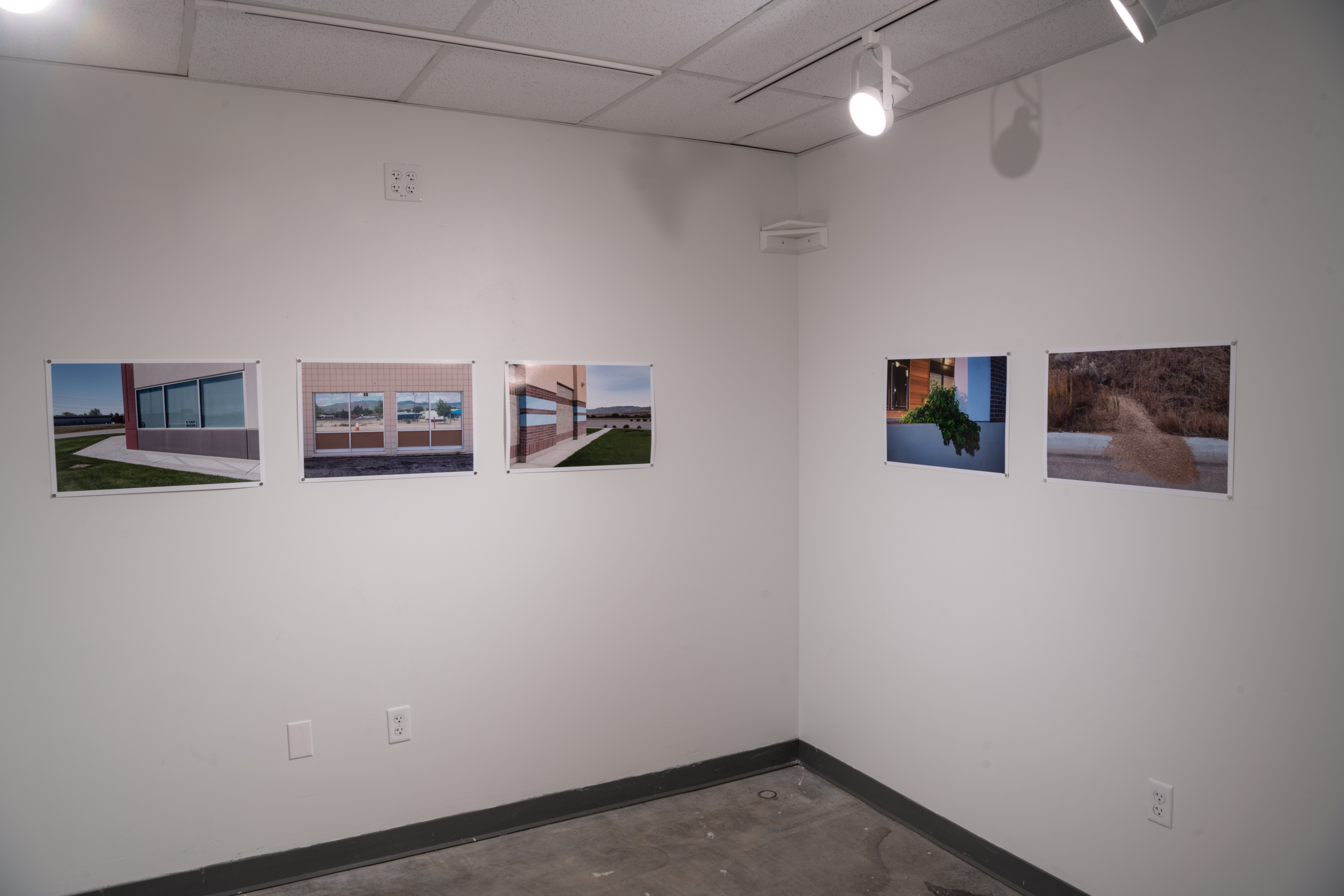 Gallery installation of Untitled 14 small prints showing 3 photos at left and 2 at right.