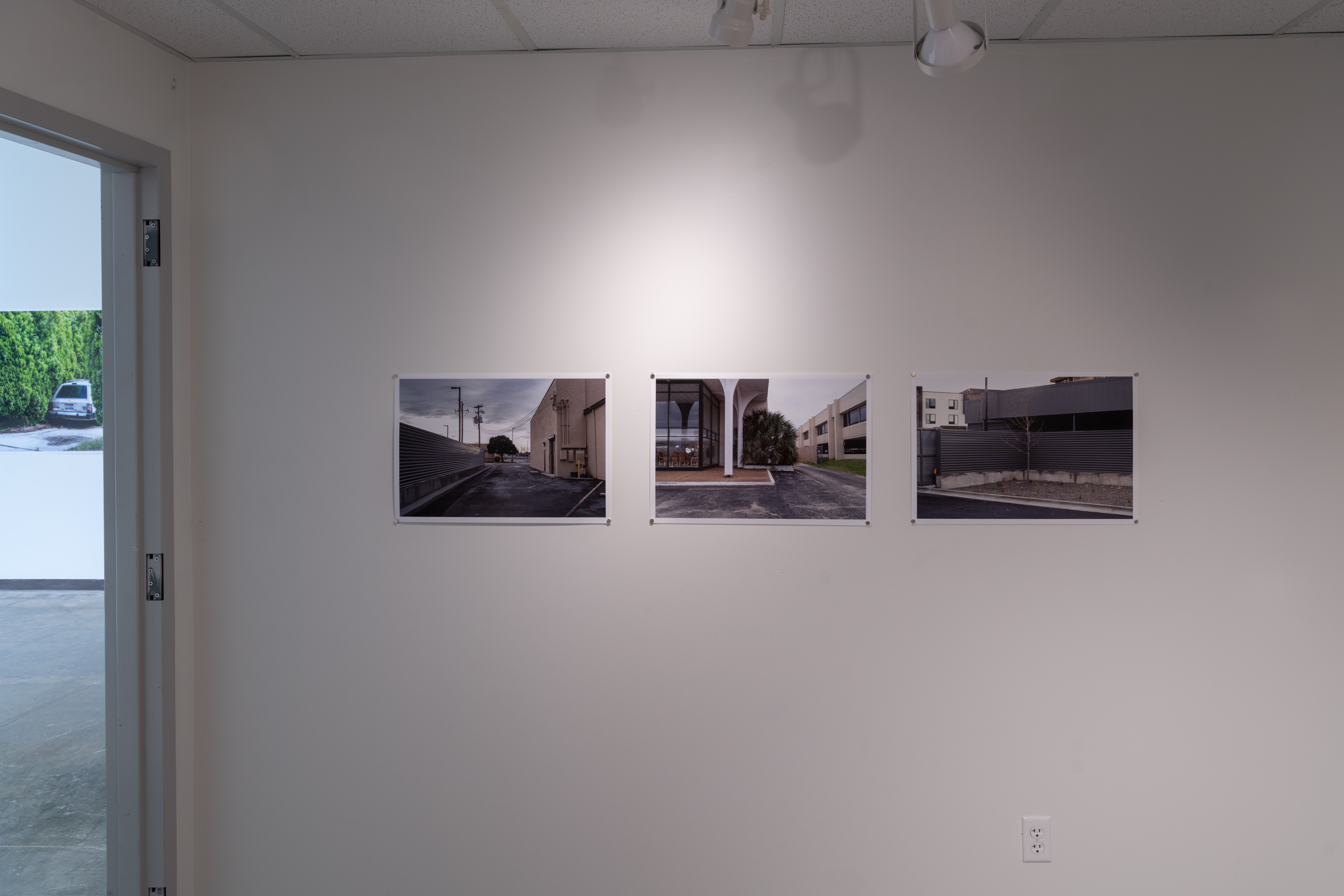 Gallery installation of Untitled 14 small prints showing 3 photos hung in a horizontal line.