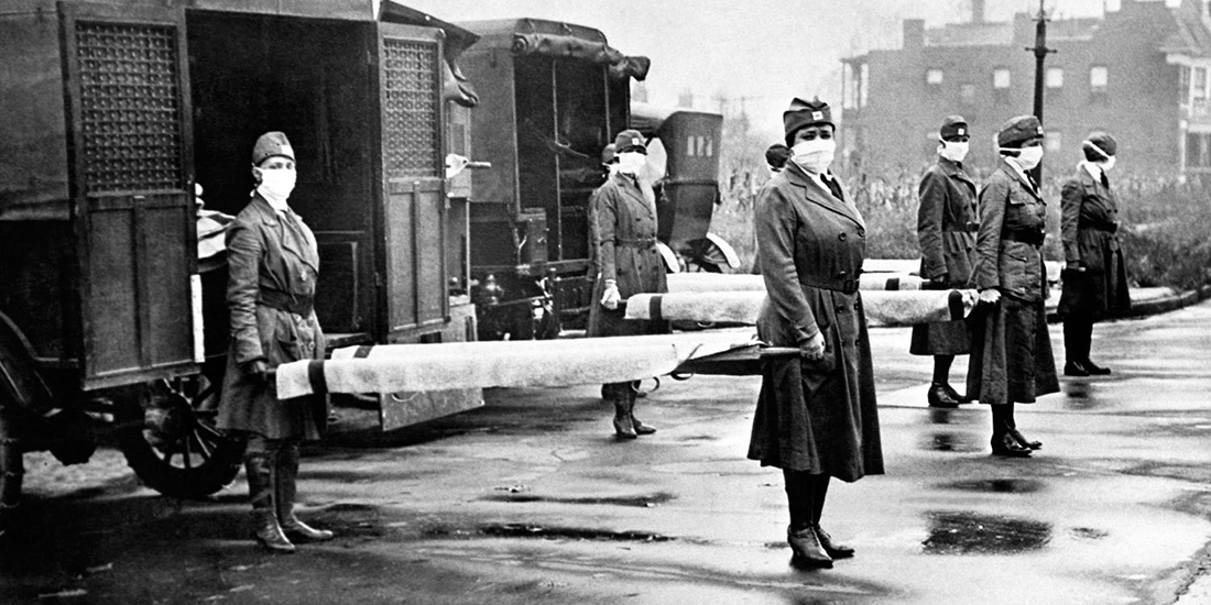 Nurses hold stretchers in front of ambulances