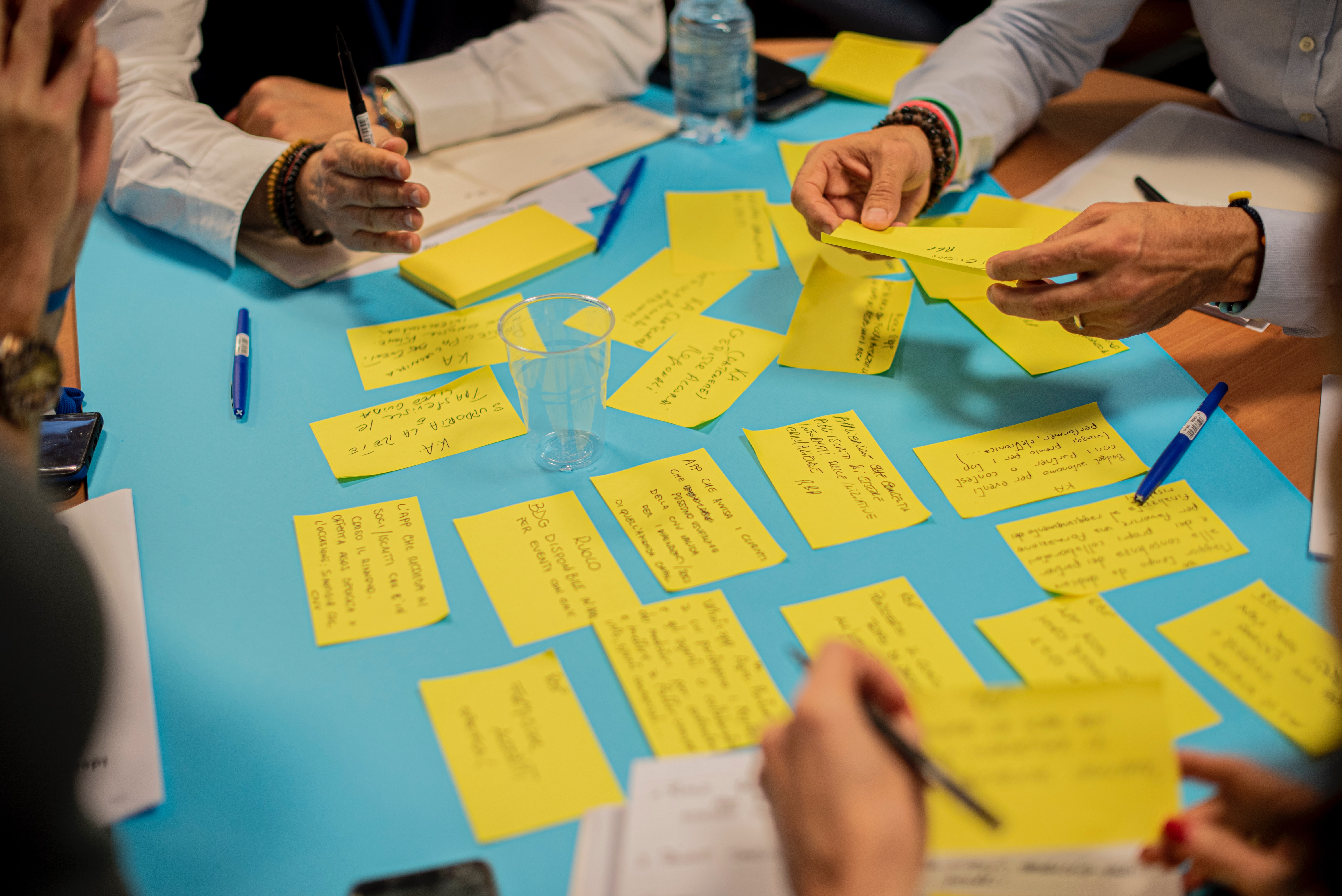 People writing on sticky notes at a table