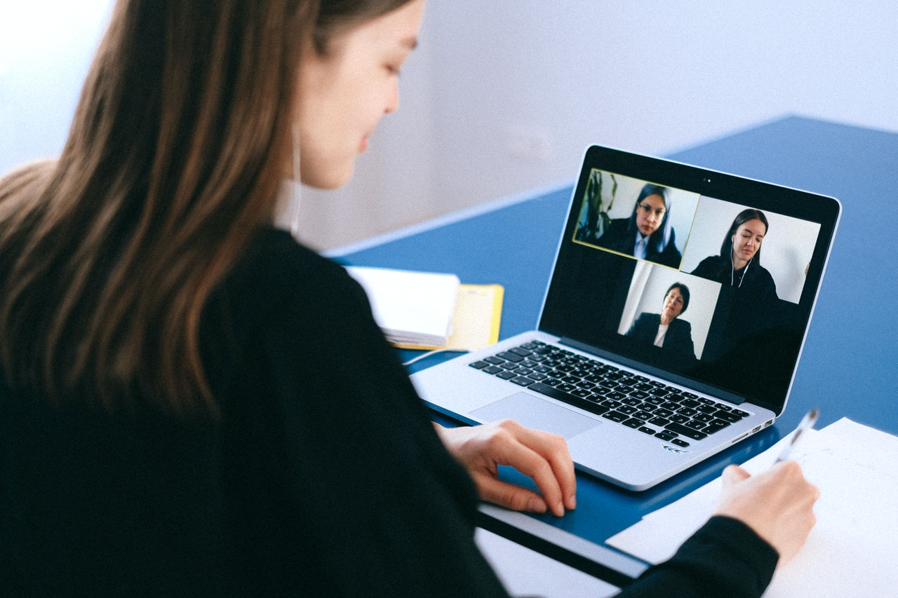 Woman in black suit jacket on video conference on laptop