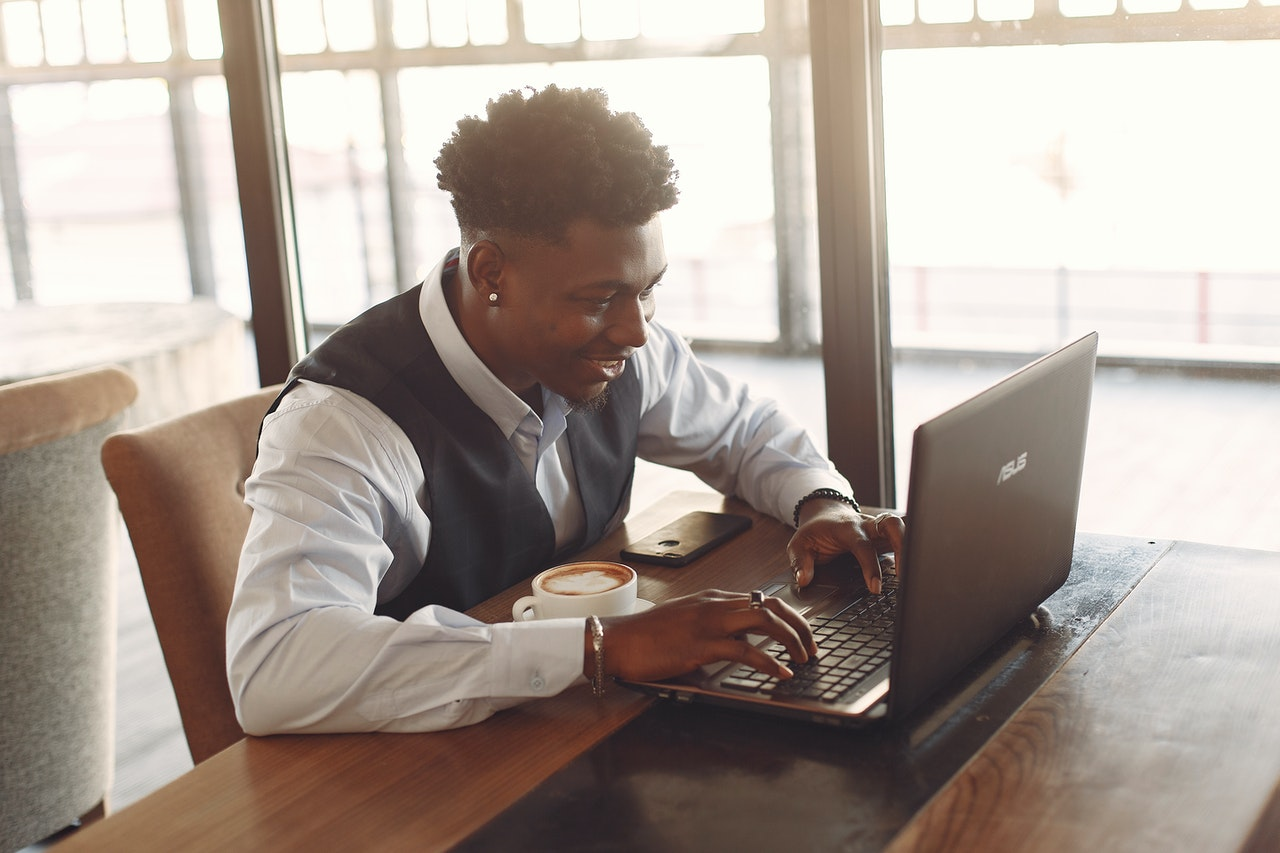 Black student in dress shirt and vest working on laptop