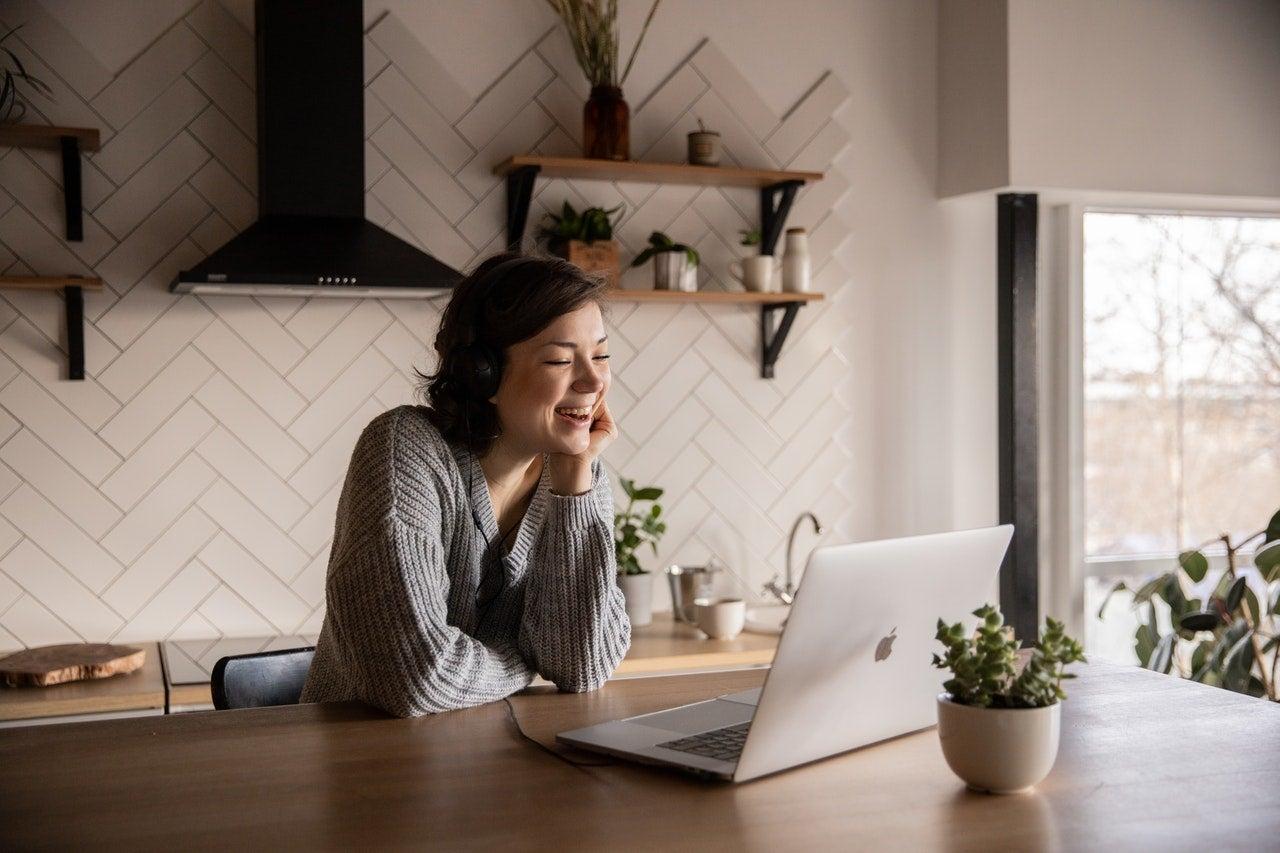 Woman in kitchen smiling at laptop