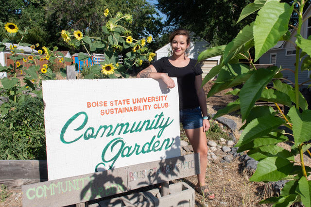Student standing next to Community Garden sign, smiling