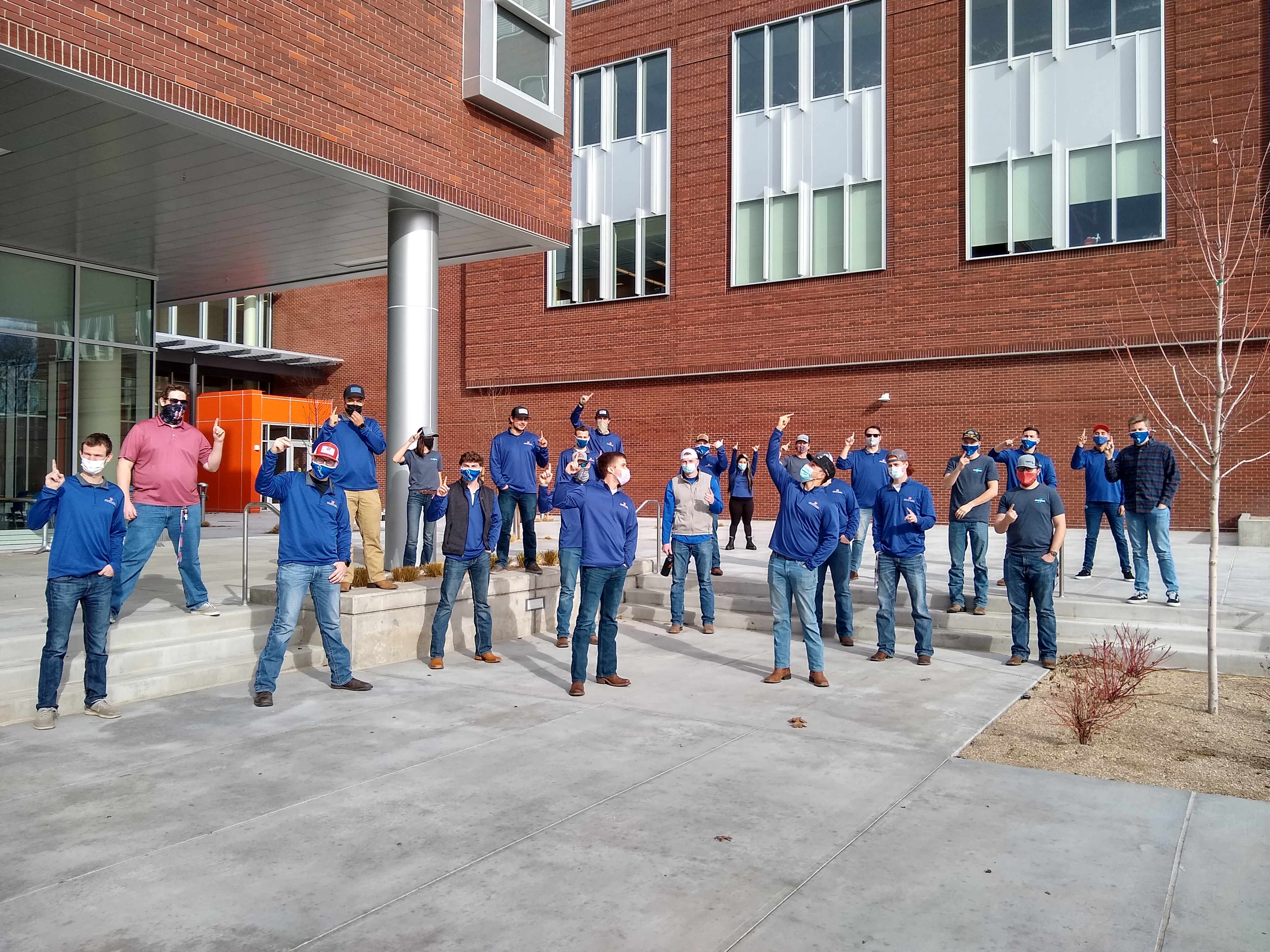 Construction Management students stand outside building, physically distanced and wearing masks