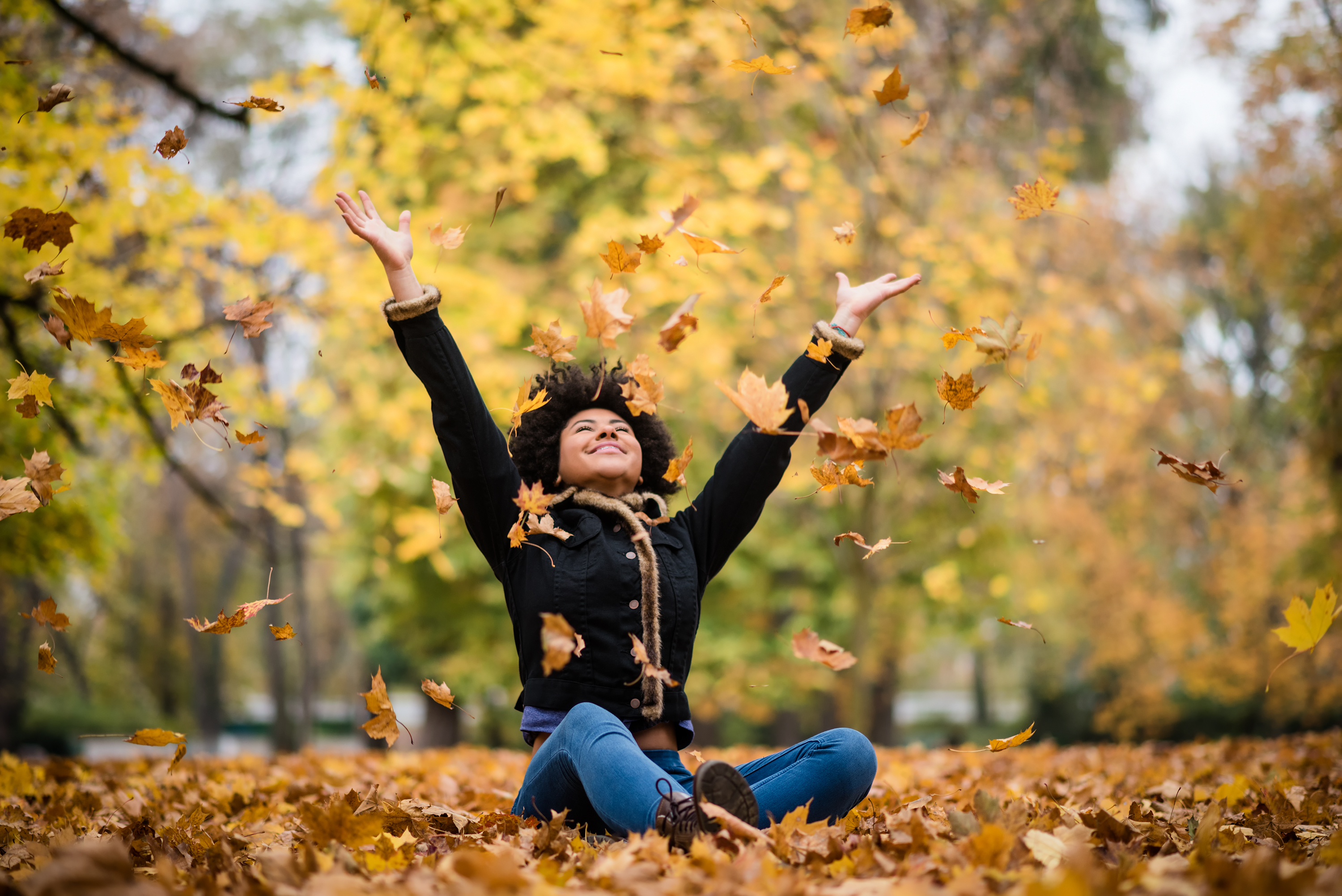 Student sitting in fall leaves and throwing leaves in the air