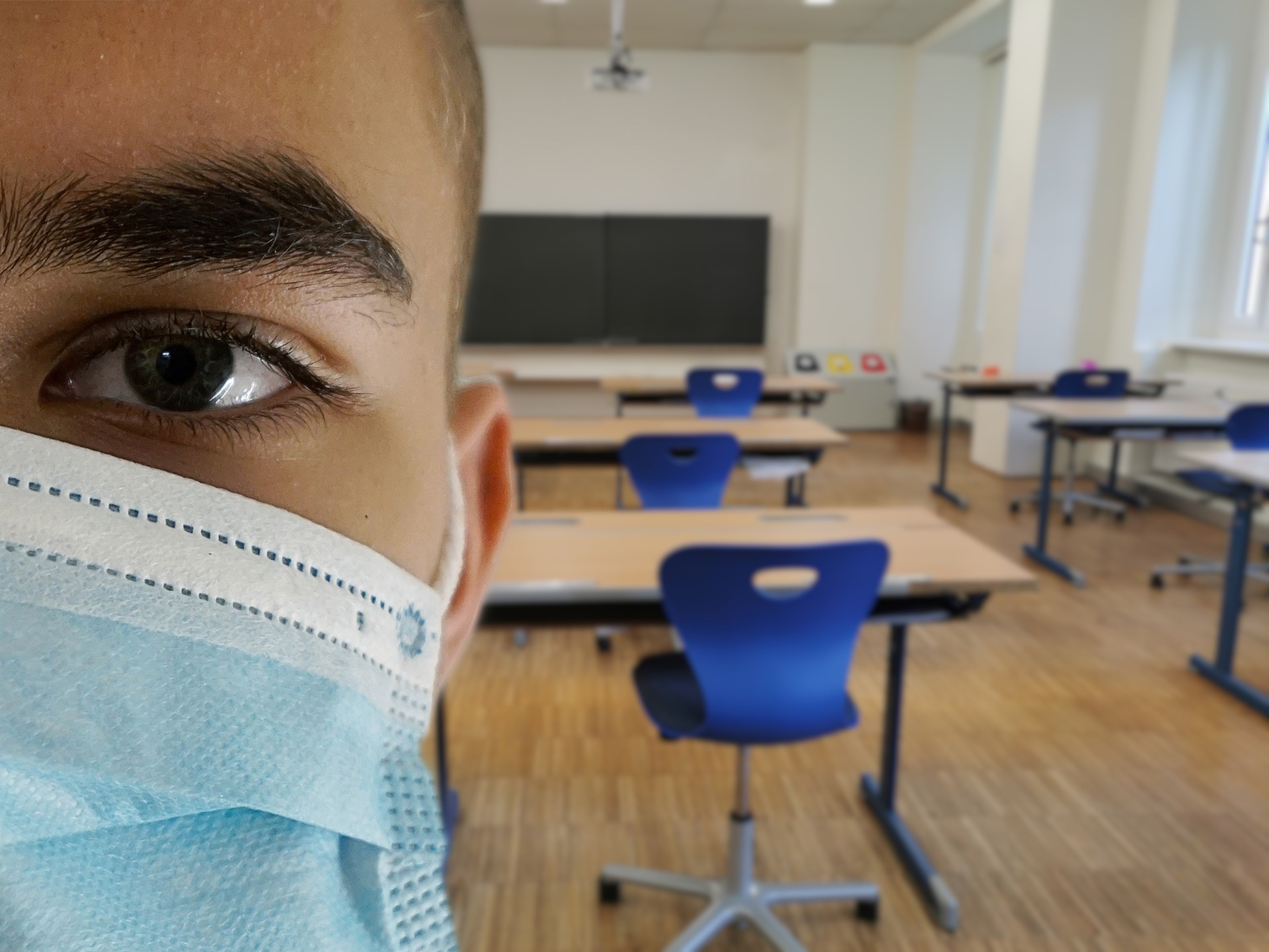 face of student wearing mask with empty classroom behind them