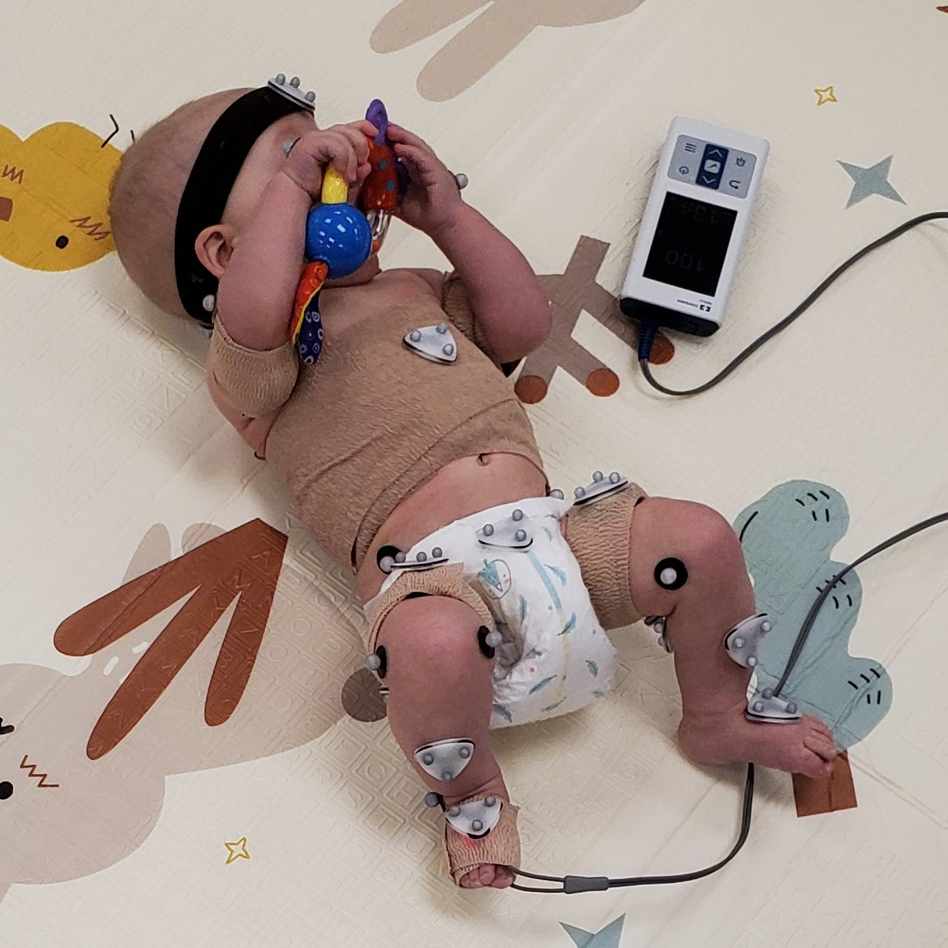 infant with sensors on play mat