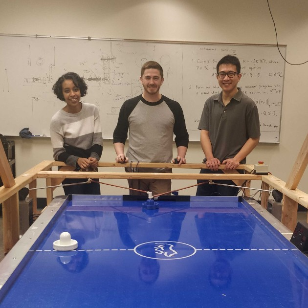students with robot controlled air hockey table