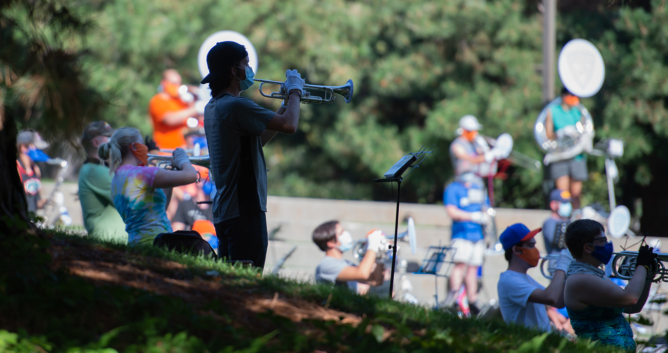 student plays the trumpet in a mask and socially distanced