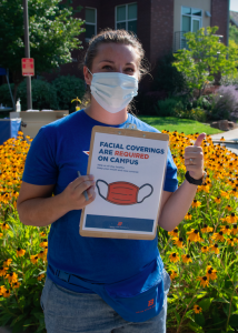 """Masked woman holding sign that reads """"facial coverings required on campus"""""""