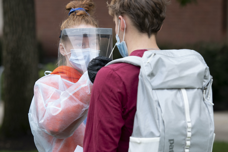Student in PPE gives nasal swab