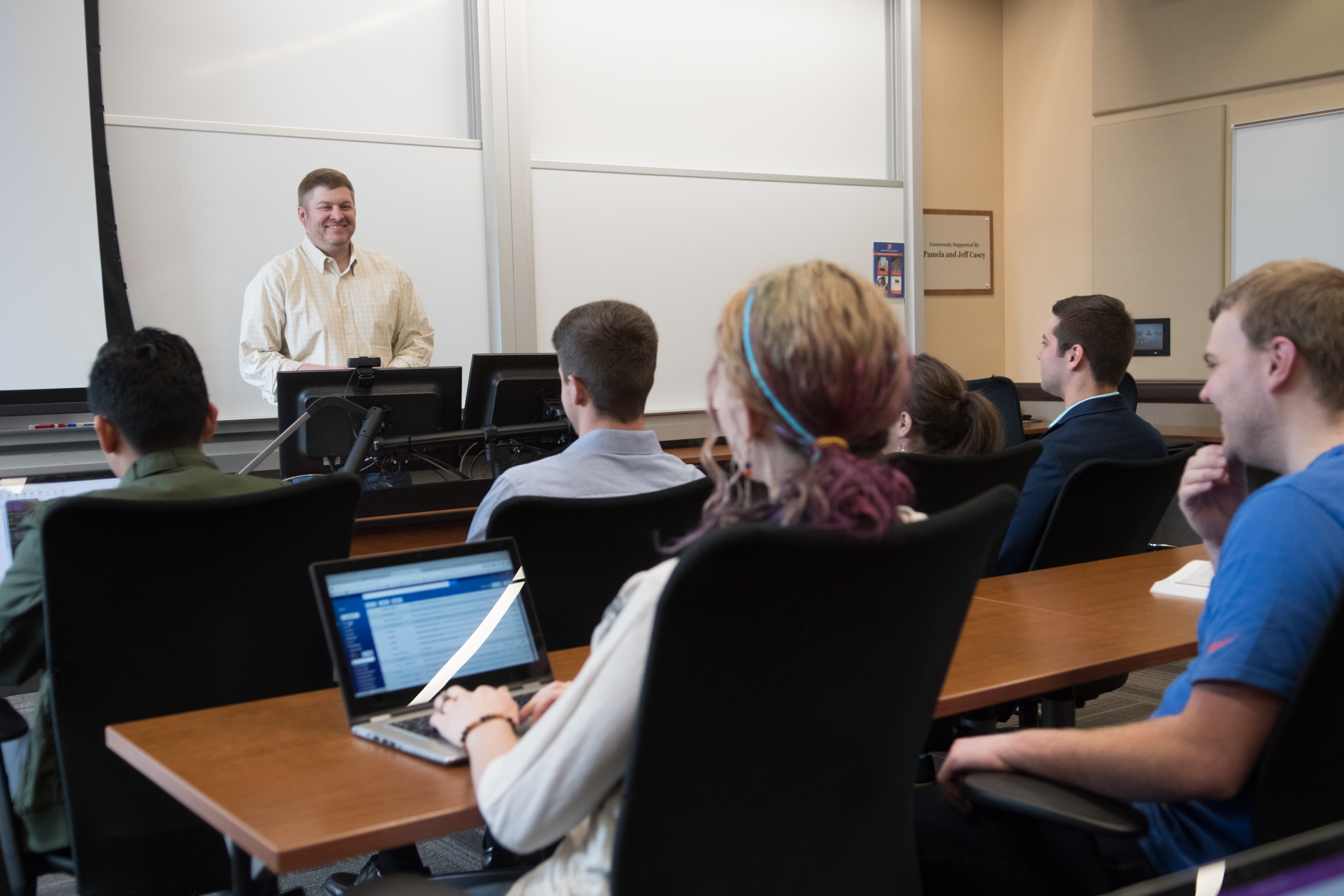 An instructor speaks in front of his students