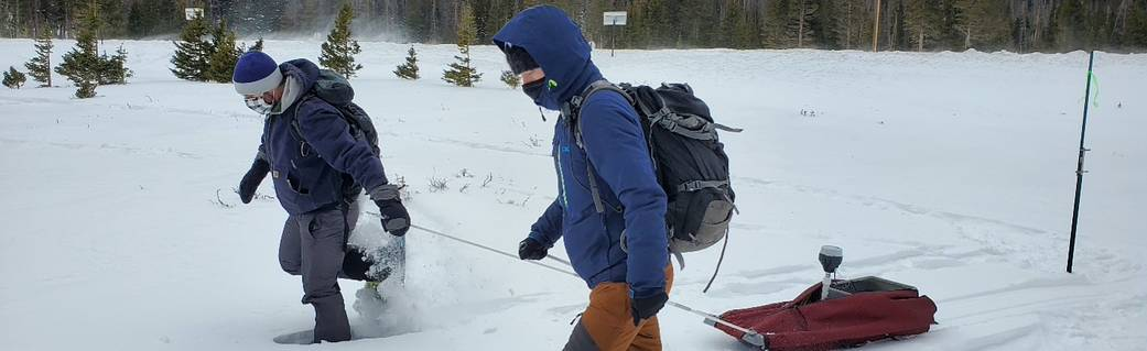 two people in snow gear, pulling sled with equipment through the snow