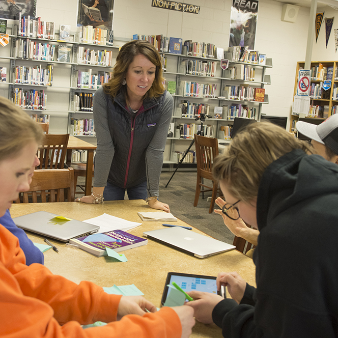 Teacher working with students at a table using an ipad