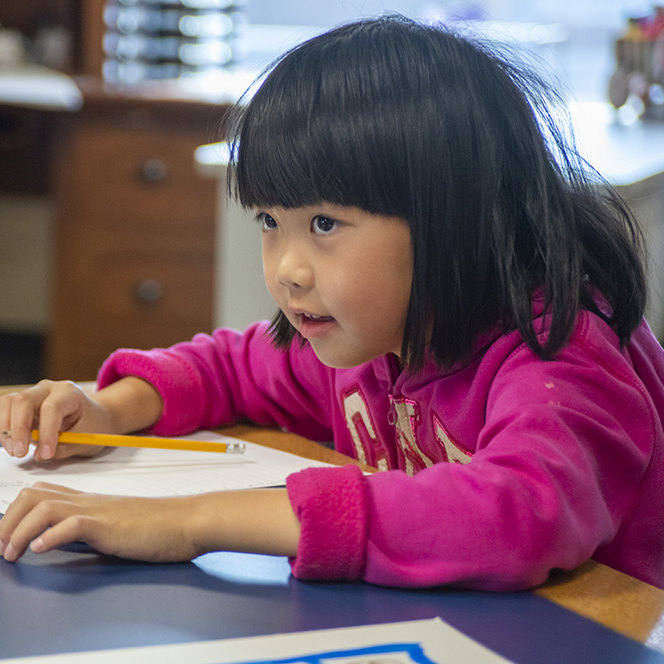 Elementary student at a table with paper