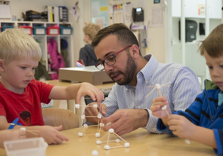 Photo of teacher with children at a table building a marshmallow and toothpick molecule model