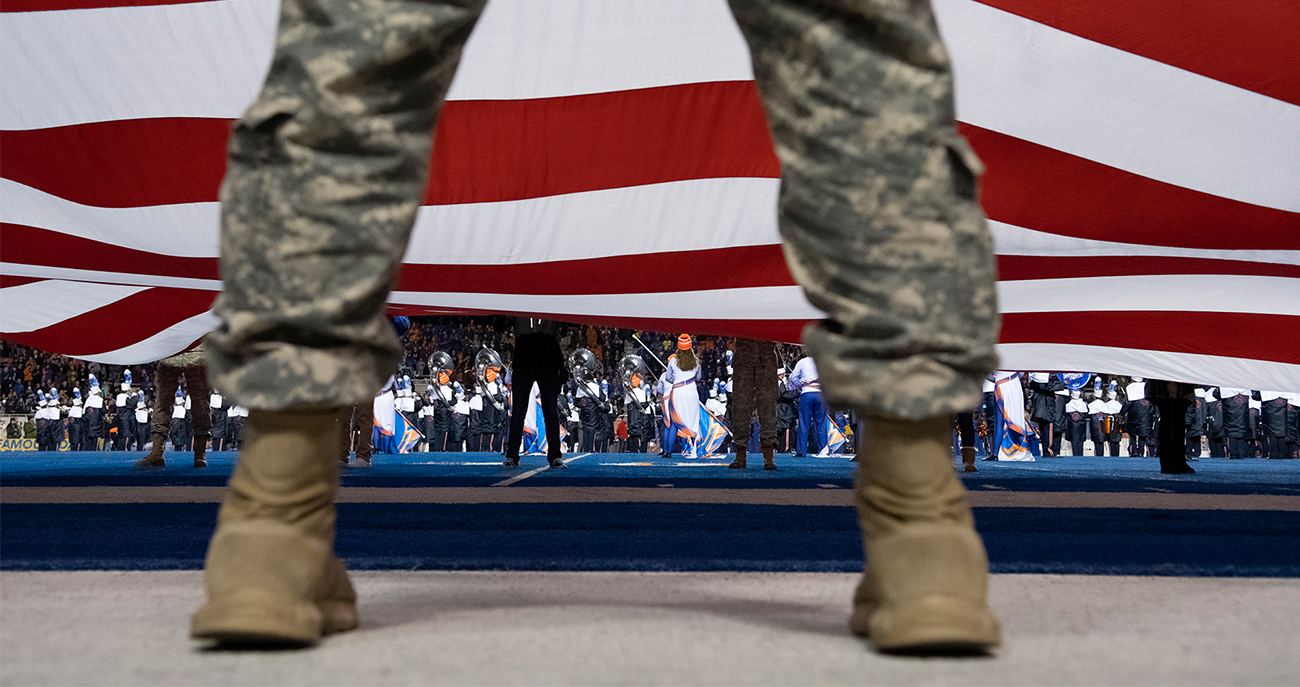Service member in front of flag