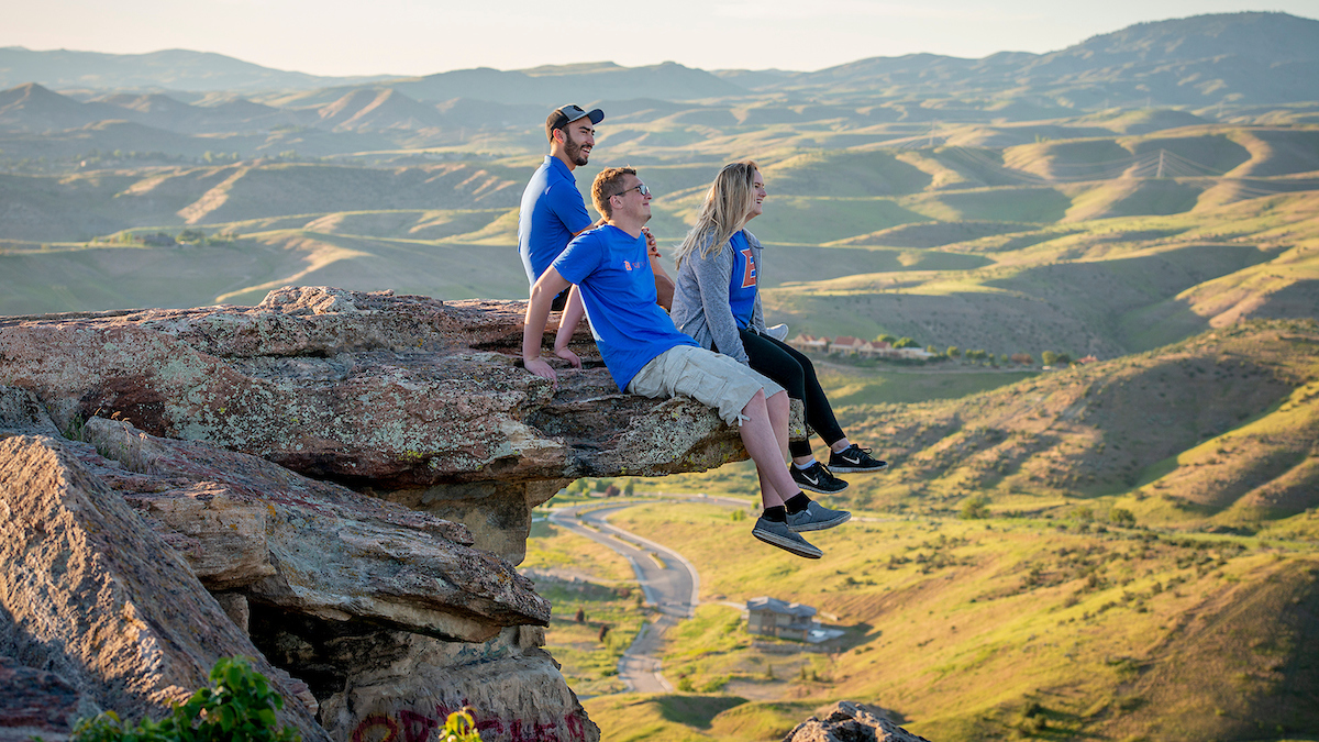 Three people sit on a rock overlooking the Boise foothills