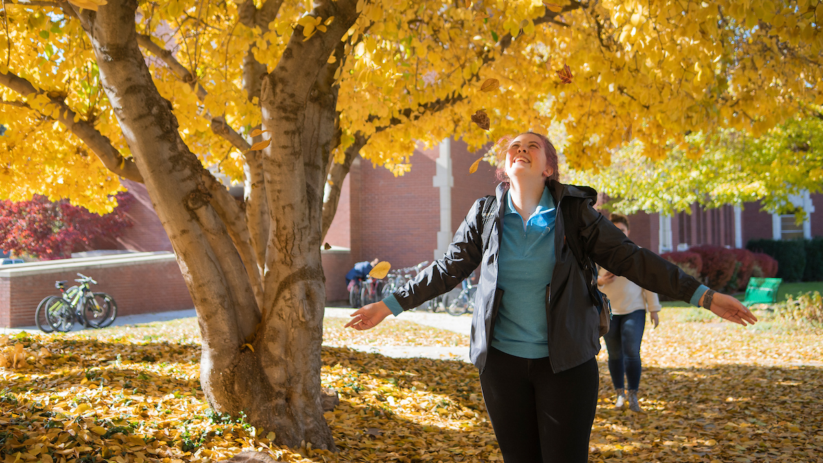 Young woman standing under fall free smiling
