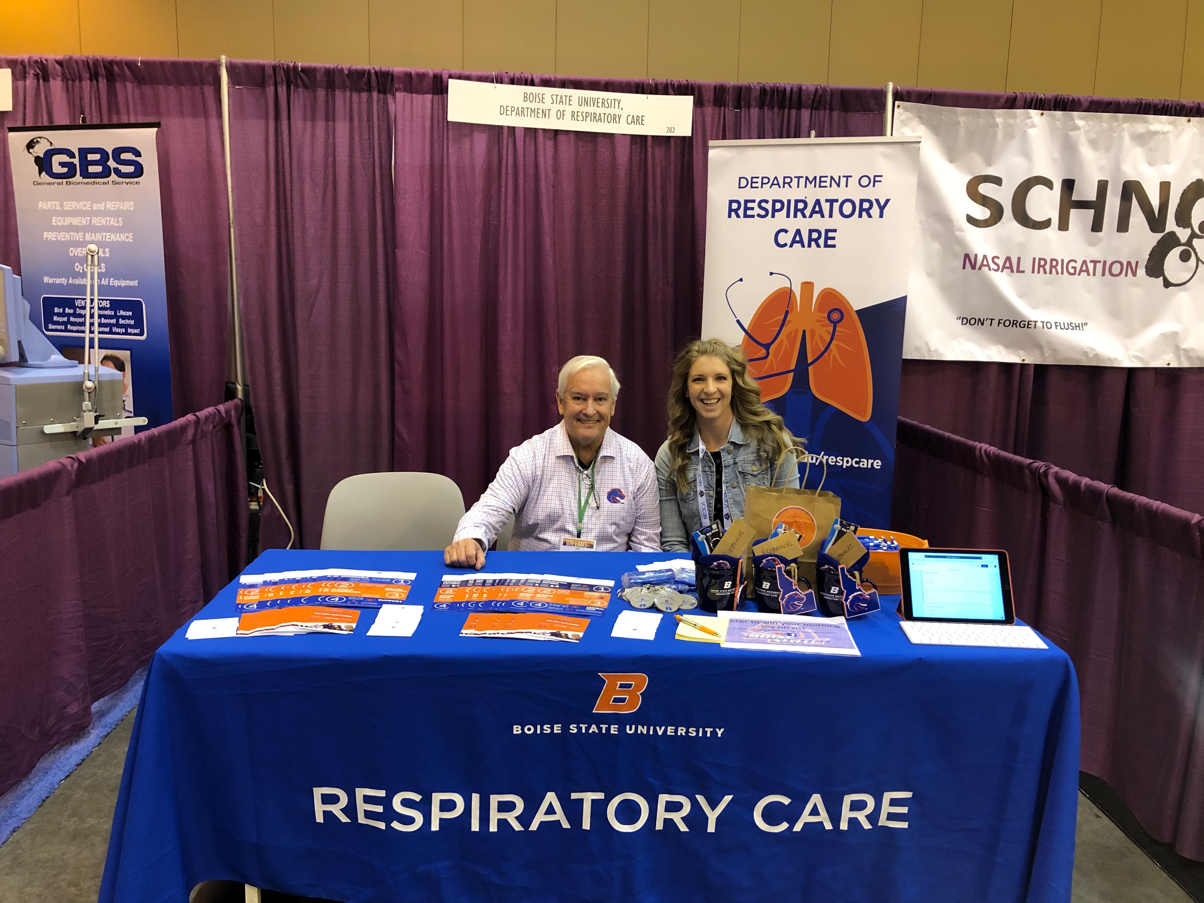 "Faculty sitting at a table at the event that reads ""Respiratory Care"""