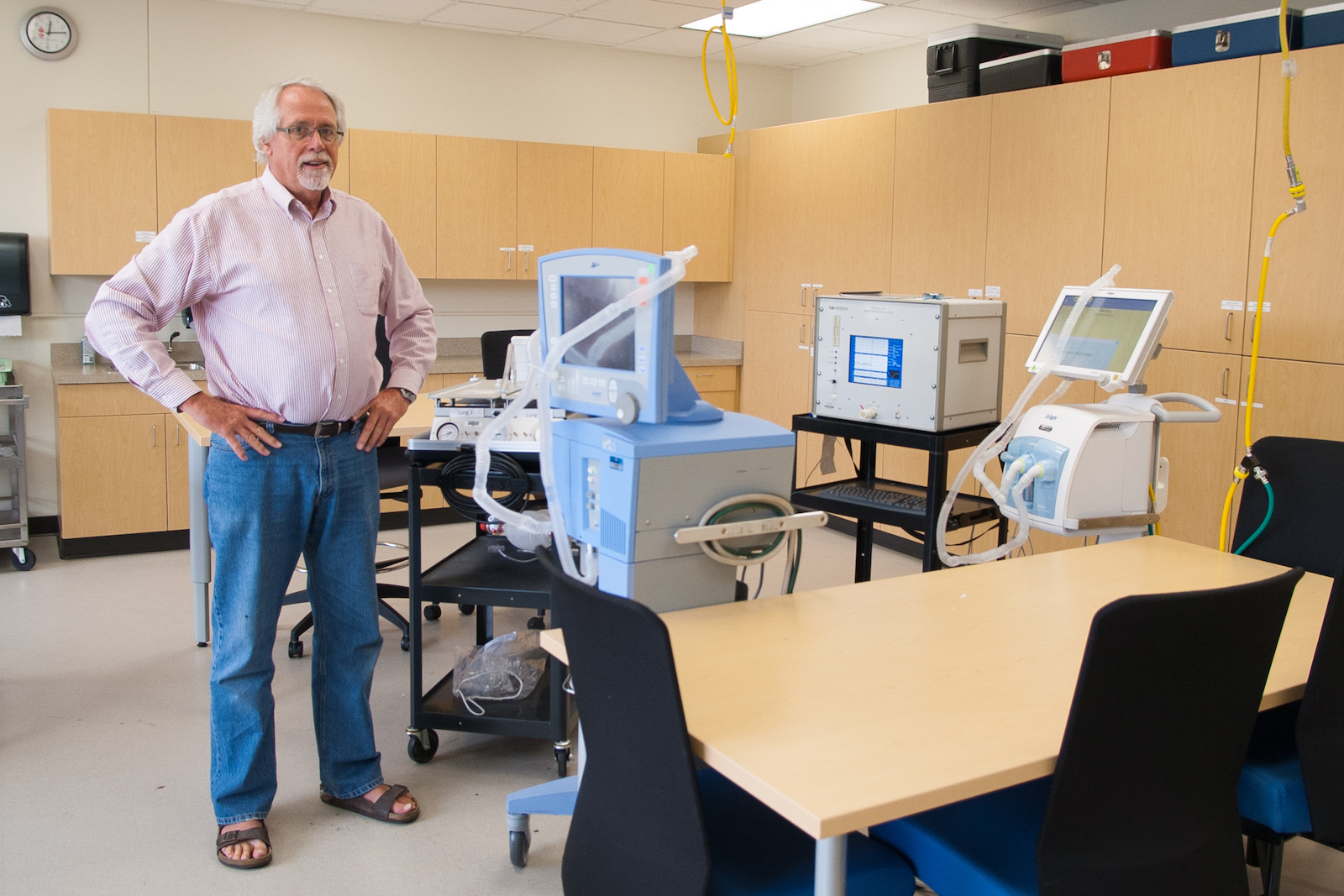 Respiratory Care faculty Lonny Ashworth stands in lab with ventilators