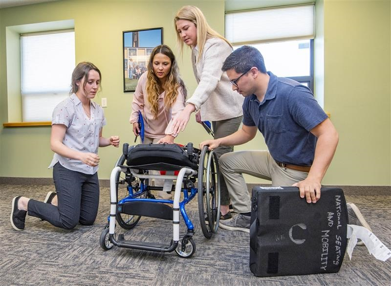 Students working with a patient in a wheelchair