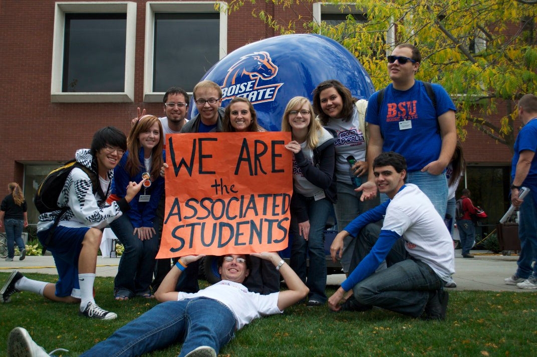 """Students pose in front of Helmet cart and hold sign that reads """"We are the Associated Students."""""""