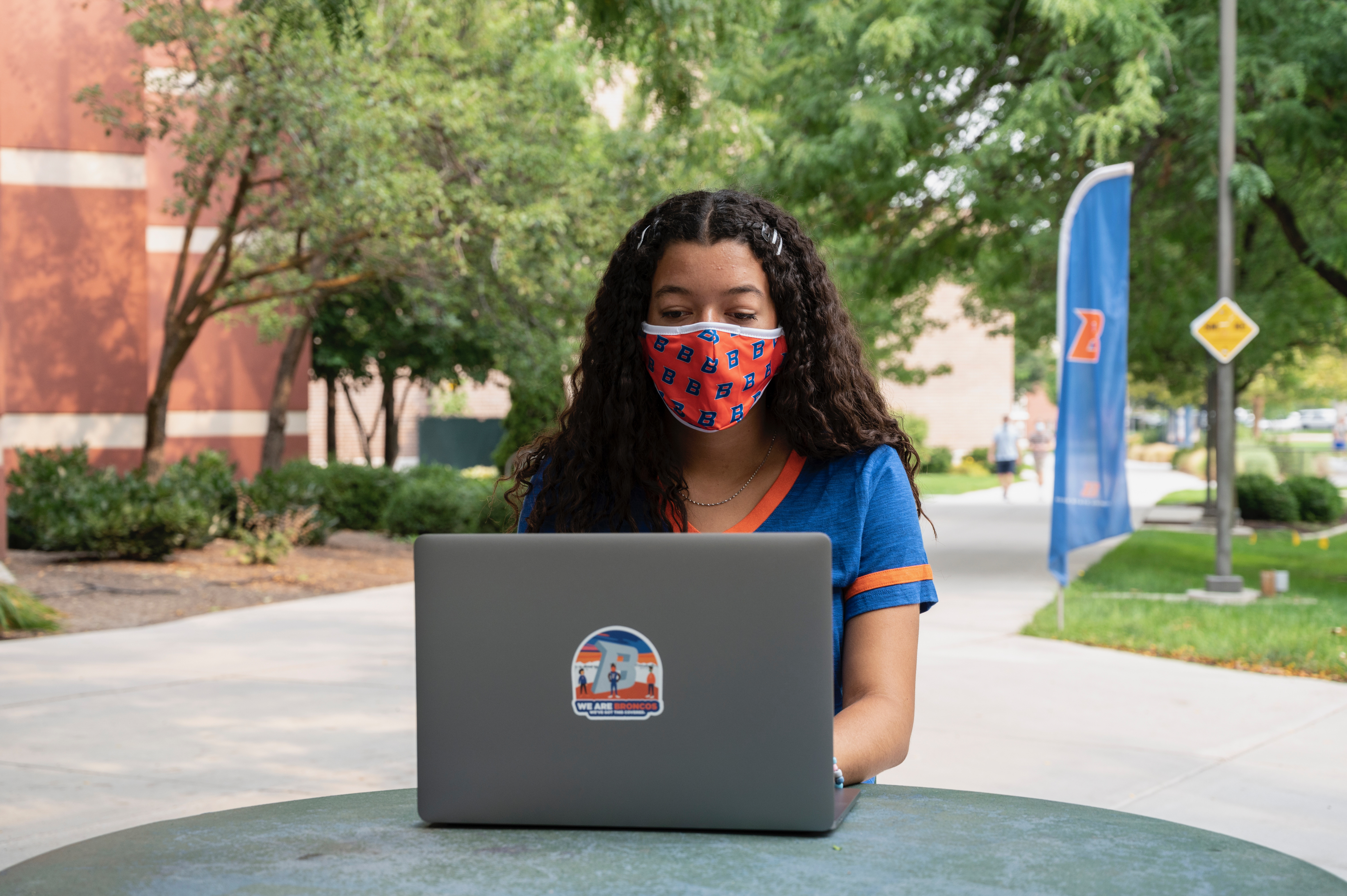 Female student wearing facial covering sits outside on campus and works on laptop