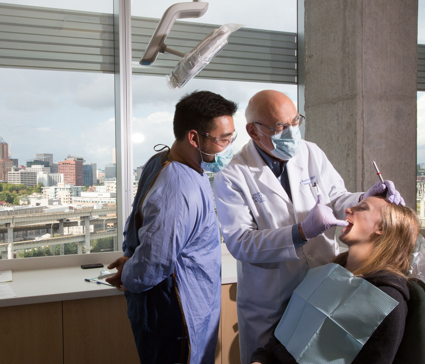 Two dentists helping a patient in a chair