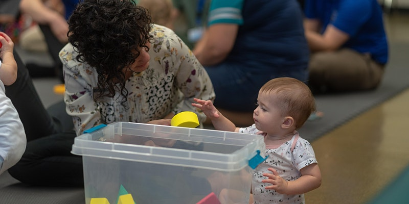 Occupational therapist handing toys to children