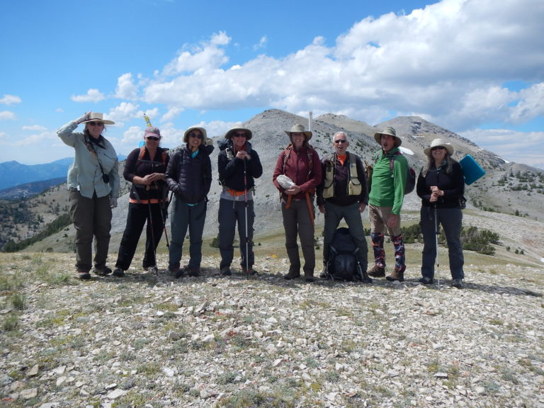 Team of scientists posed on a mountain summit (photo by Beth Corbin)