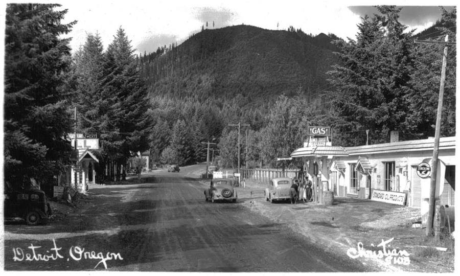 Black and white phote of gas station surrounded by mountains and pine trees, cars driving on dirt road in front of the station