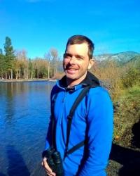 Christian wearing binoculars standing near a mountain lake