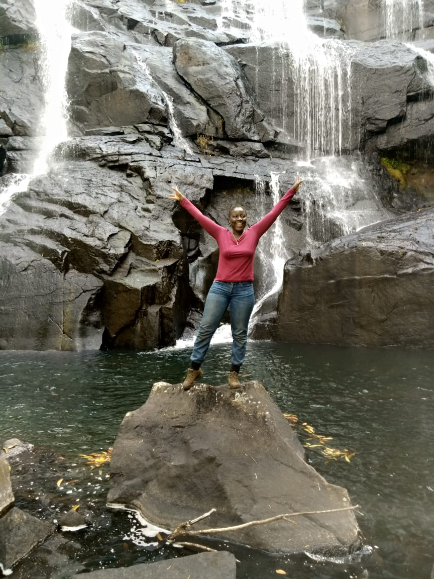 A black woman stands with arms raised joyfully in front of a cascading waterfall