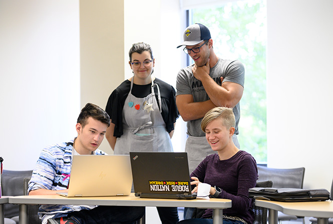Two students using laptops with two MakerLab employees supervising them.