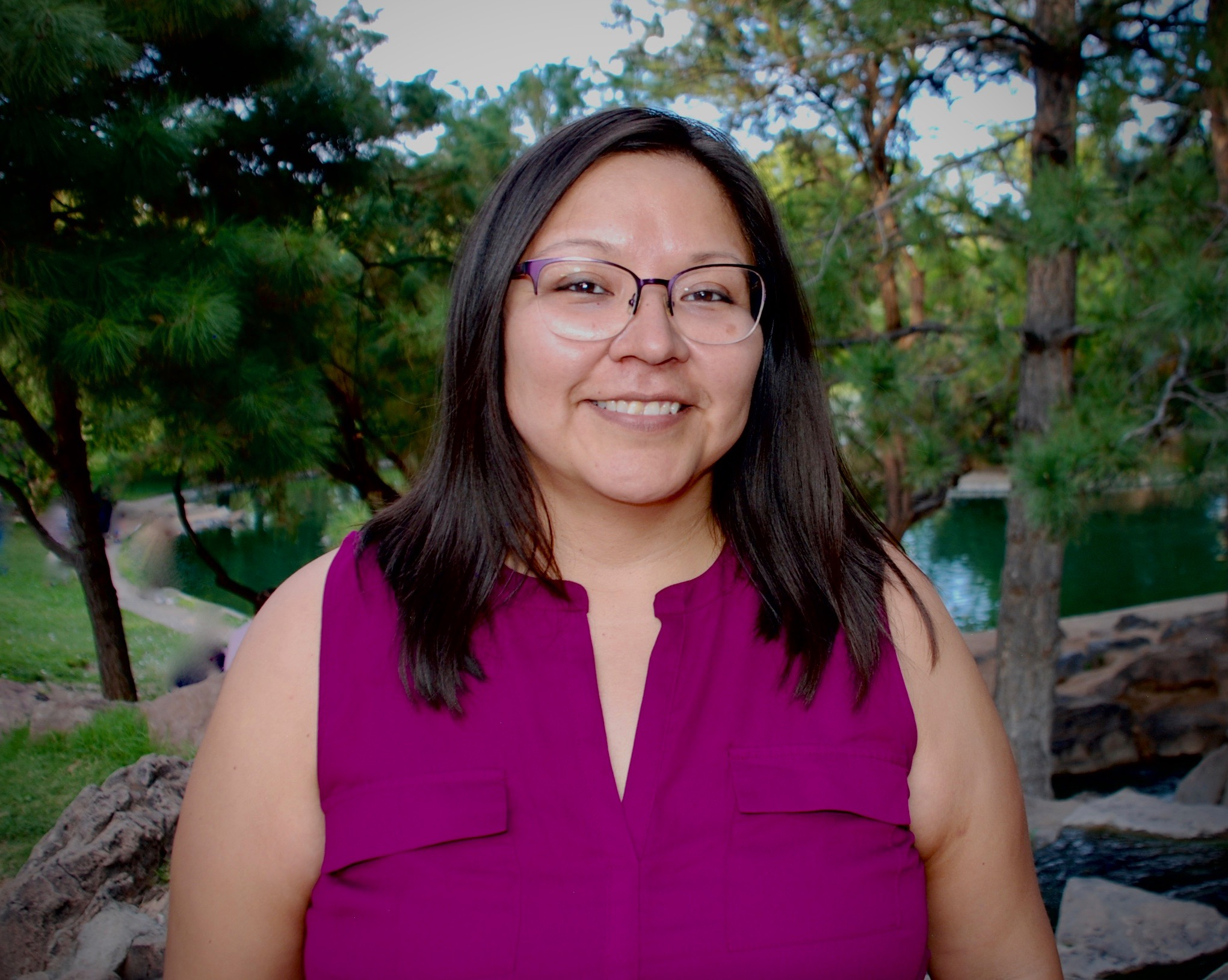 profile picture featuring Adrienne Tsikewa with a with trees in the background