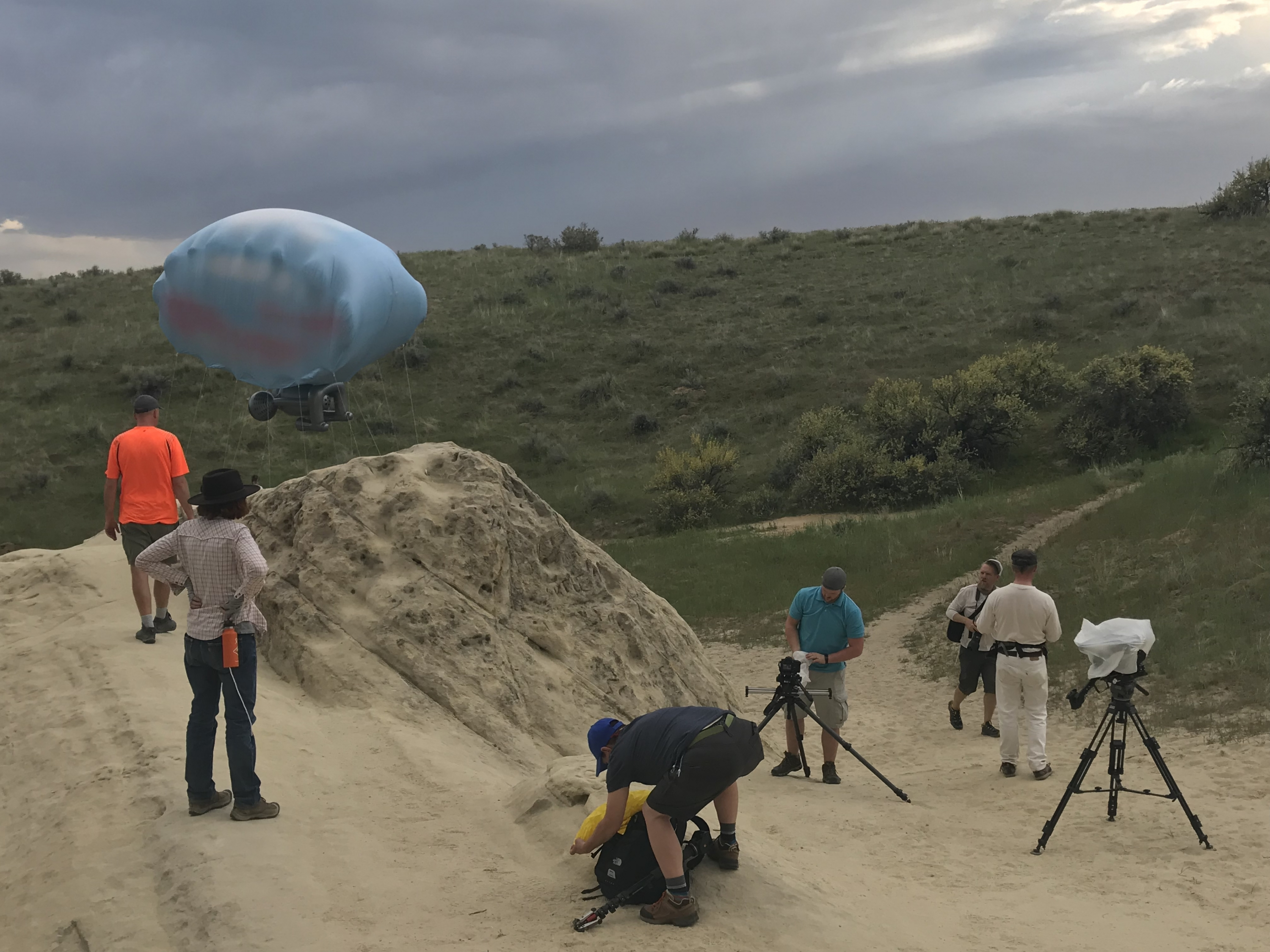 Camera crew setting up around Cloudship performance art in the Boise foothills