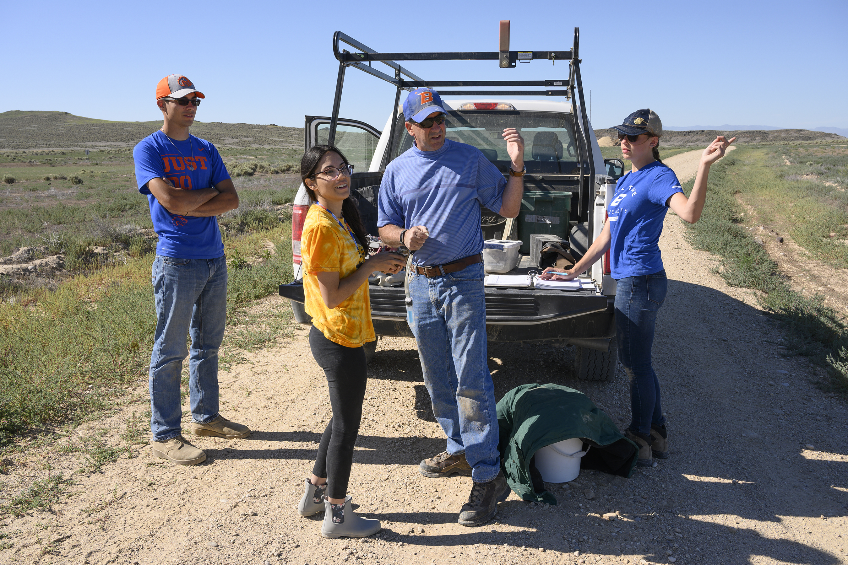 Jim Belthoff and research students stand behind truck on dirt road