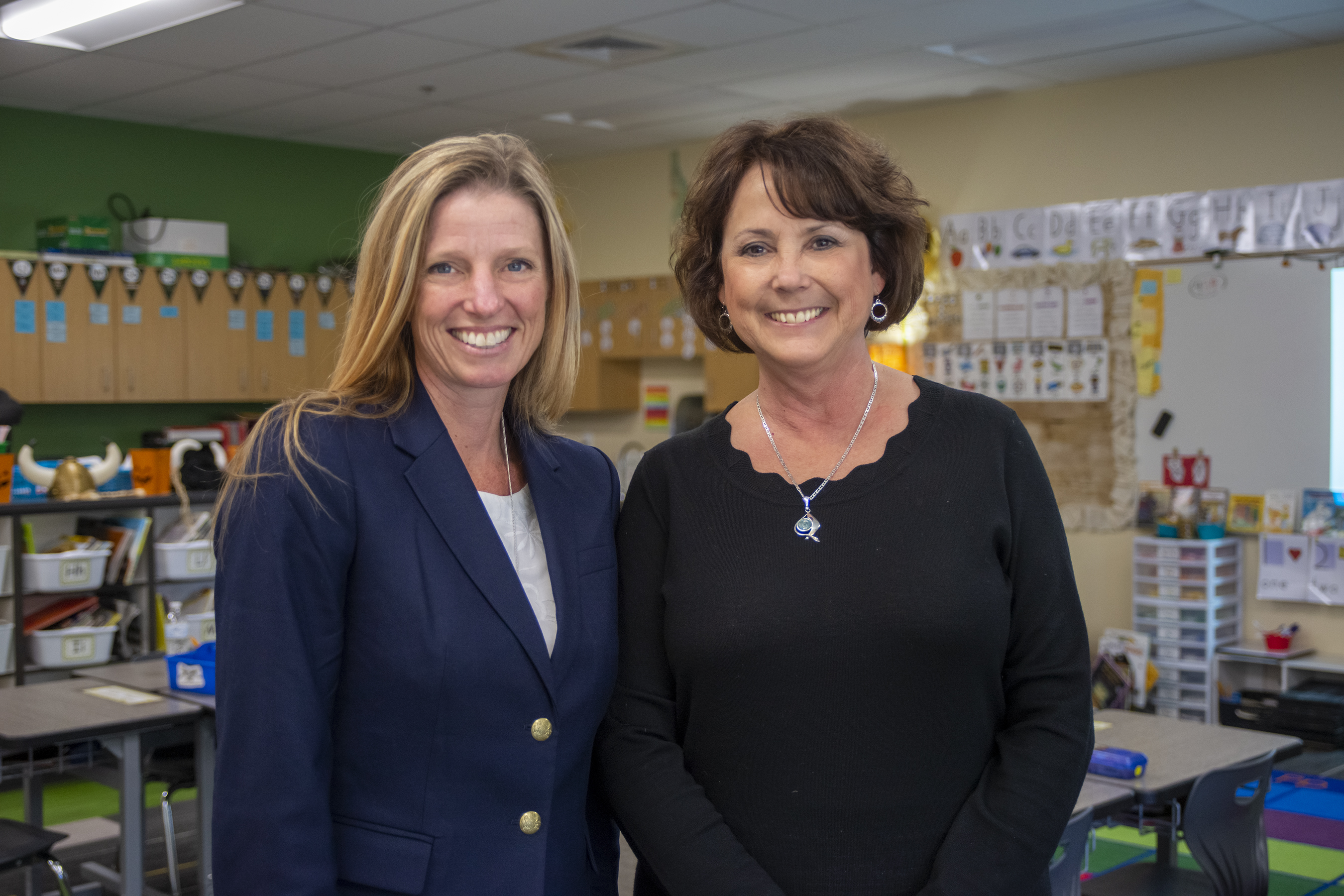 Two researchers pose in a children's classroom