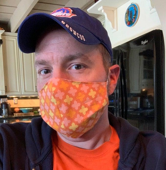 Man wering orange patterned protective face mask
