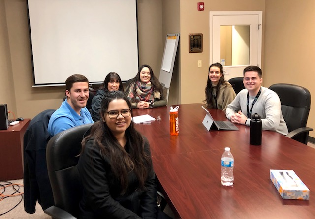 Students smile around a conference table