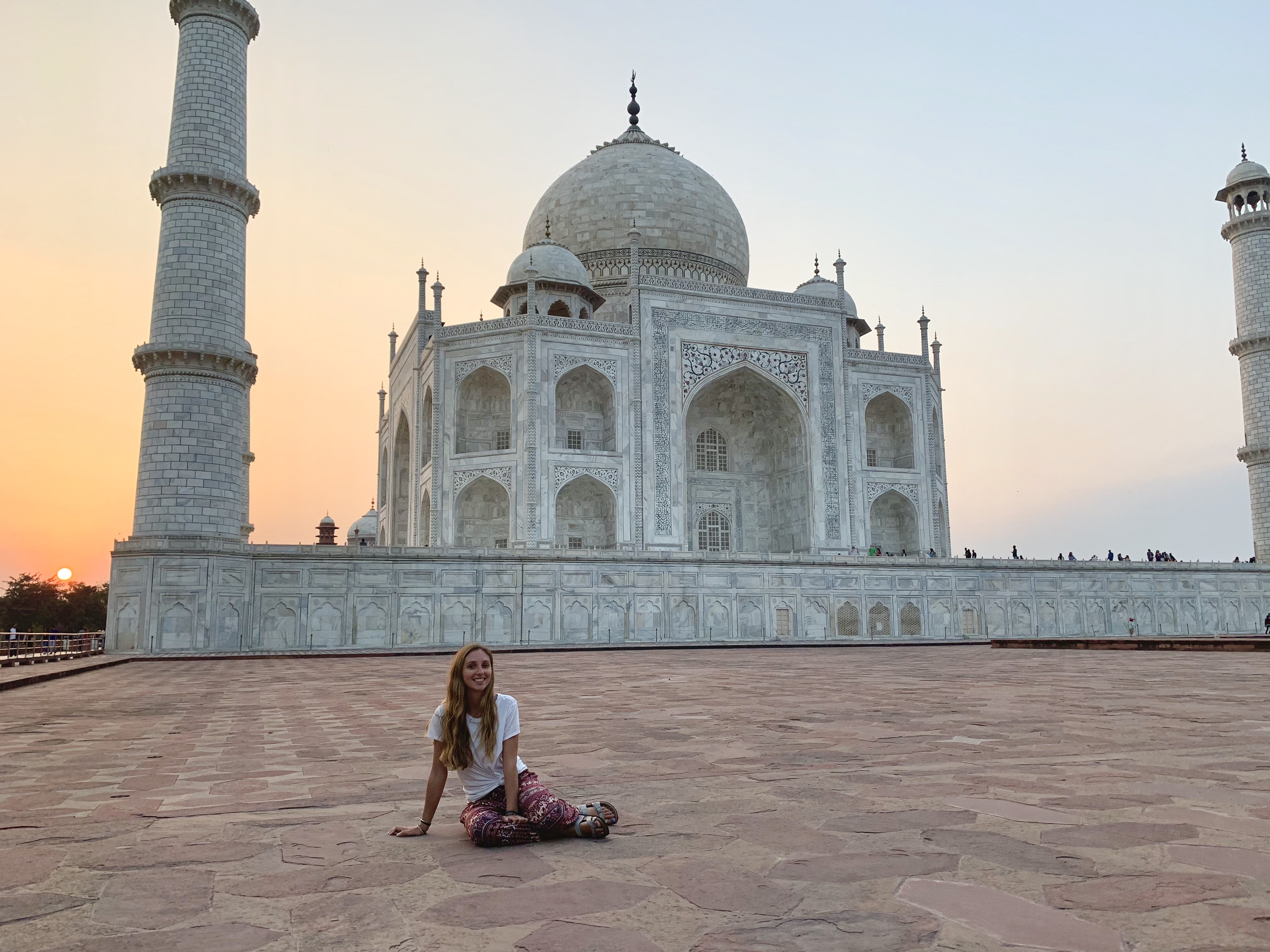 A woman poses in front of the Taj Mahal