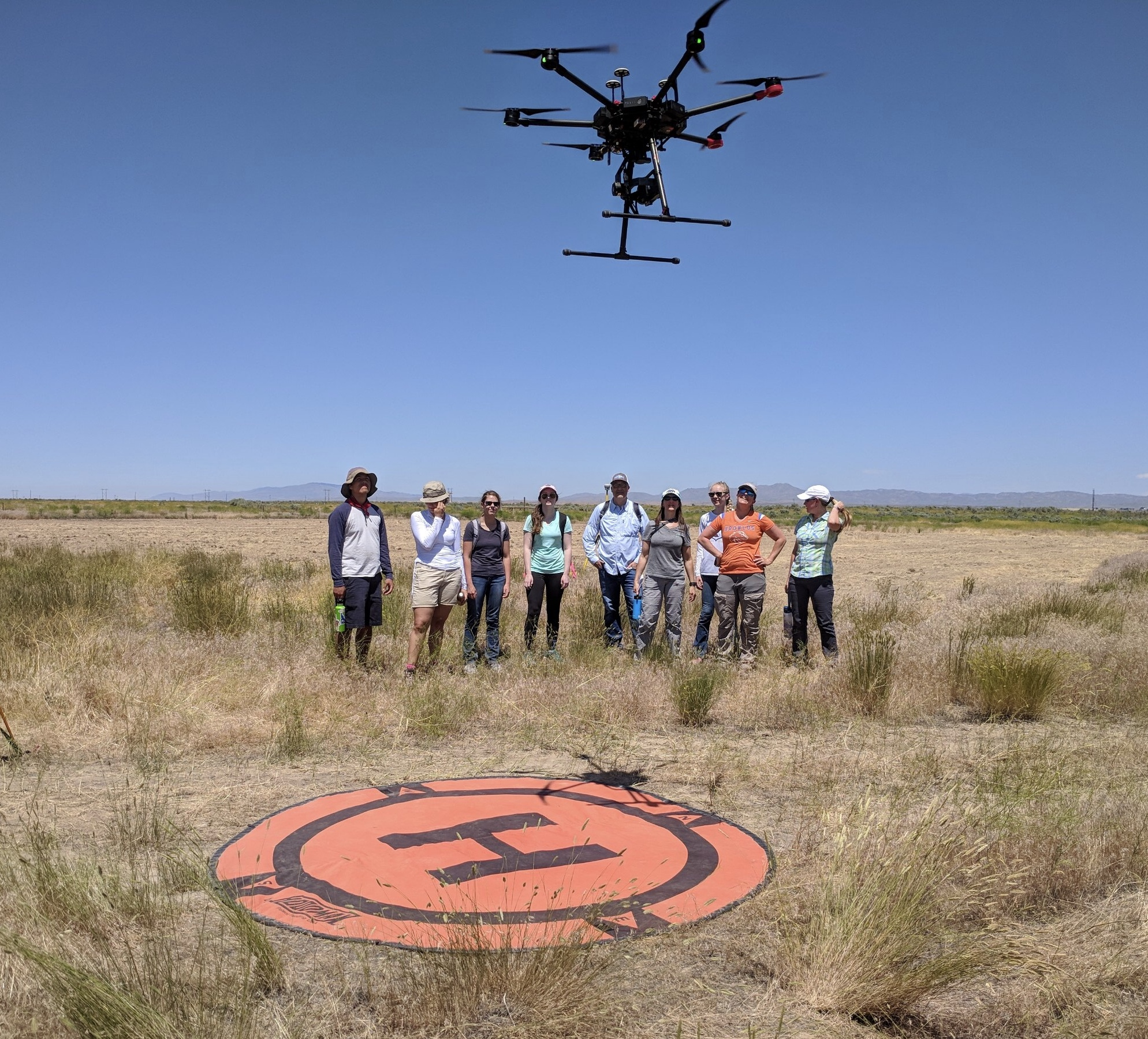 Group of people in rangeland watch drone ascend